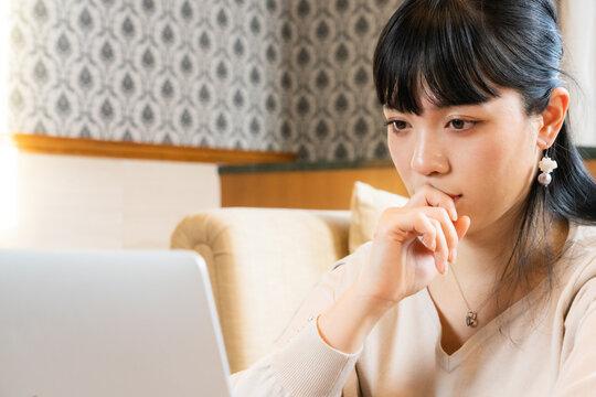 ノートパソコンの画面を見て考える女性