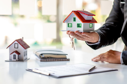 Real estate broker agent presenting and consult to customer to decision making sign insurance form agreement, buy and sell home model, concerning mortgage loan offer for and house insurance