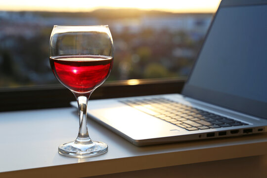 Glass of red wine on background of laptop and window with sunset view. Alcohol for inspiration, relax after work