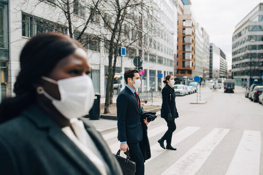 Female and male colleagues crossing street in city during pandemic