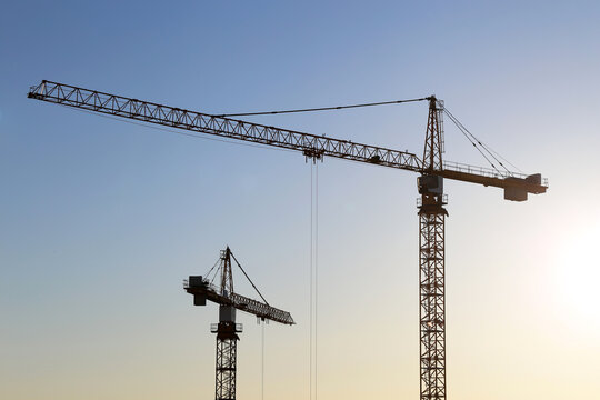 Construction cranes on blue sky and sunrise background. Housing construction in city