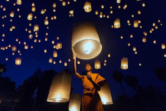 Little monks lit a fire of floating lantern,Thai Buddhist Monks float lanterns