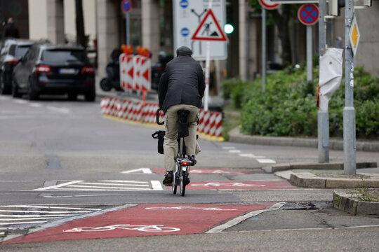 fahrradfahrer auf einem radweg richtung baustelle in der stadt