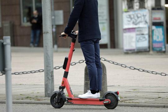 mann mit einem e-scooter in der stadt
