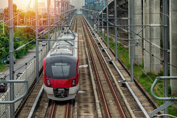 Electric train on the railway. Electric train  red-white  color  on railway in Bangkok, Thailand. New  Electric train in Bangkok, Thailand.