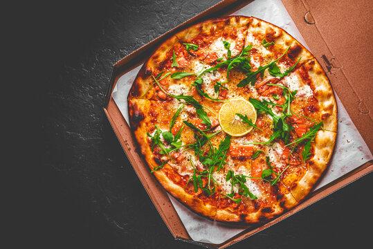 Pizza with Mozzarella cheese, salmon fish, tomato sauce, arugula, lemon. Italian pizza on Dark grey black slate background