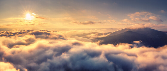 Aerial view of mountains in orange clouds at sunrise in summer. Mountain peak in fog. Beautiful landscape with rocks, hills, sky. Top view from drone. Mountain valley in low clouds. View from above