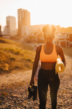 Young female athlete with sports shoe and exercise mat standing on land during sunset