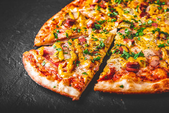 Pizza with Mozzarella cheese, backon, ham, tomato sauce, pepper, sausage, pickled cucumbers and onion. Italian pizza on Dark grey black slate background
