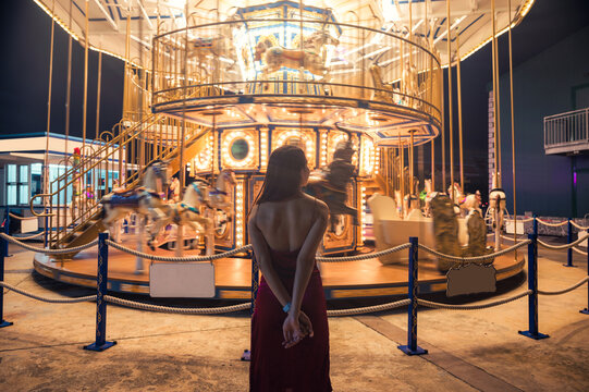 Young asian woman in red dress standing in glowing carousel at amusement park