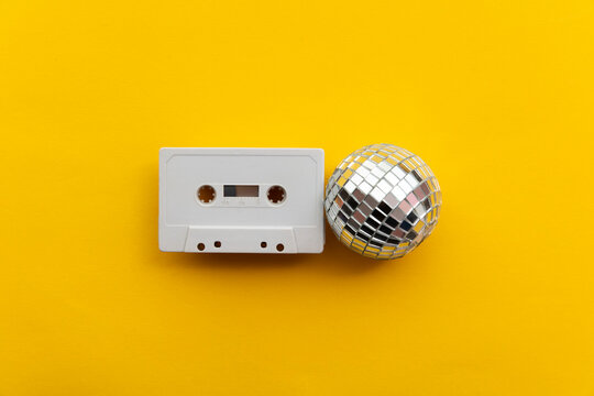 Retro disco glitter ball with a vintage cassette tape