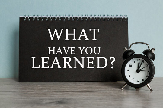 A word WHAT HAVE YOU LEARNED on black notebook with clock. Concept for time management and business.