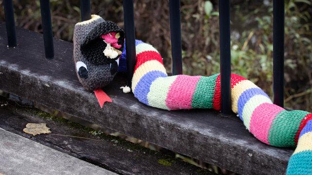 Dayboro, Australia - May 3 2021: Yarn bombing, cute wool snake wrapped around the poles of a bridge.