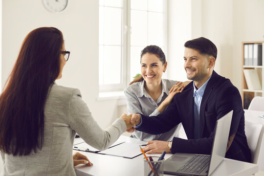 Female bank employee shakes hands with a happy married couple after successfully signing documents. Couple consults with an insurance agent or lender in the office. Business ethics concept.