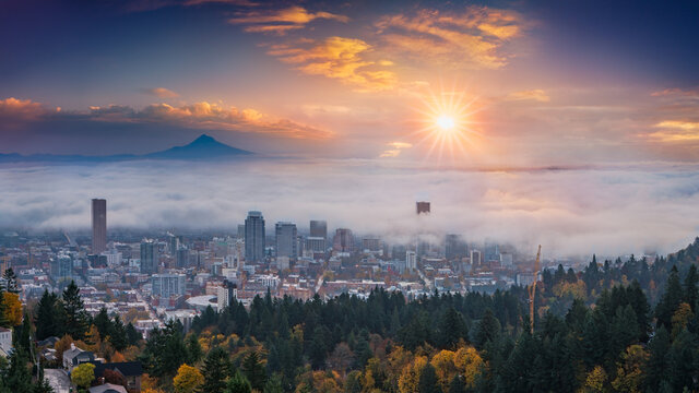 Mt. Hood and Portland downtown with rolling fog and autumn foliage in shining sunrise and colorful clouds