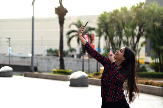 latina girl takes a selfie outside a shopping on a sunny day behind palm trees