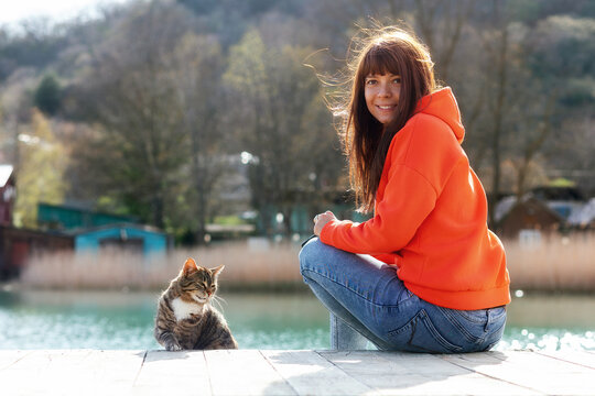 A female volunteer sits on a bench near a stray hungry cat. A shelter worker takes care of the street animals. Rear view. Outdoor. Concept of protection and care of stray animals