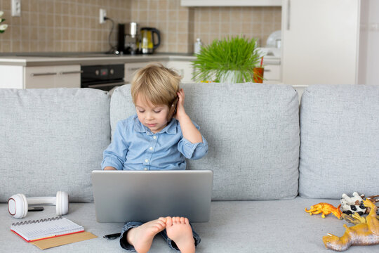 Sweet blond child, boy in casual clothes, woring on computed at home