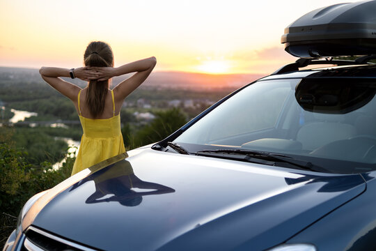 Young woman driver resting near her car in warm summer evening.