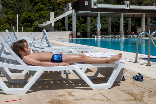 happy boy sunbathing on sun lounger during lockdown, family vacation