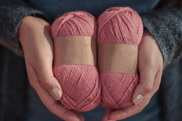 Person hands hold natural color wool alpaca yarn balls with blank labels