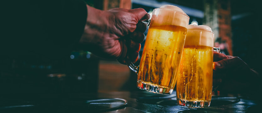 Close-up view of a two glass of beer in hand. Beer glasses clinking in bar or pub