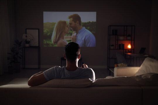 Man watching movie on sofa at night, back view