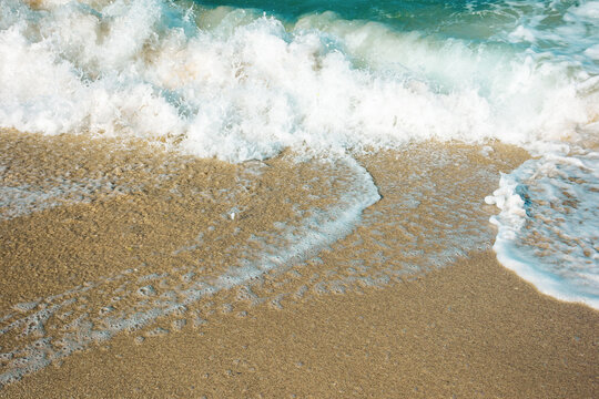 close up texture of the sea wave rolling on to the golden sandy beach. abstract nature background on a sunny summer day