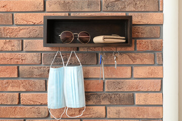 Hanger for keys with protective masks and accessories on brick wall