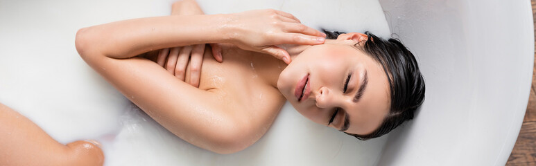 Fototapeta young woman touching neck and covering breast with hand in milk bath, banner. obraz