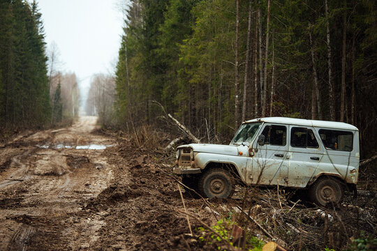 a four-wheel drive all-terrain vehicle drives through the forest through the mud. a passable SUV with large wheels and high clearance. special transport for foresters rides through swamps and mud