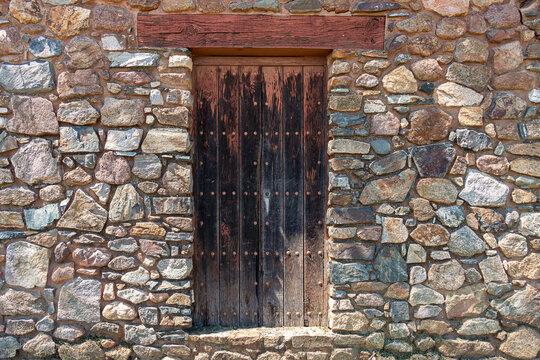 Old brown wood entrance door over rustic rock wall