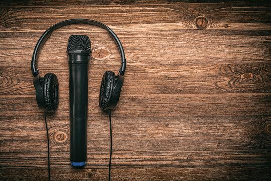 Kopfhörer und Mikrofon liegen auf einem Holztisch