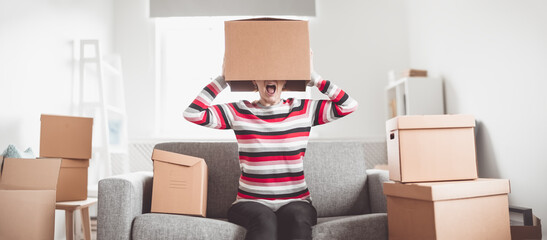 Tired woman with cardboard box on her head sitting on the sofa in her new house.