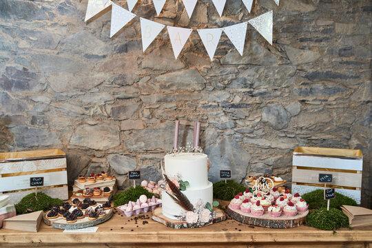 Wedding sweet bar with white cake, cupcakes, macrons