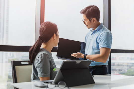 Businessman showing laptop display to woman colleague on work project.