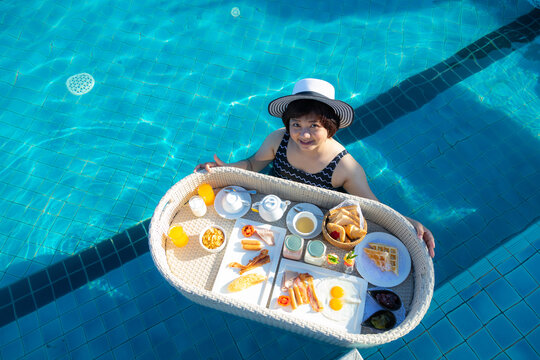 Asian woman tourists in the pool with floating breakfast for who staying on holiday, the floating brrakfast is the key tourism symbol of hotels in Phuket, Thailand.