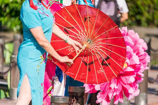 Chinese Women in Native Dress Hold an umbrella standing beside lotus lake
