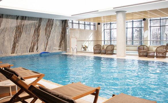 indoor pool with relaxation area - sun loungers and wicker chairs