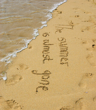 A sentence written on beach sand : THE SUMMER IS ALMOST GONE and human footprints . Vacation end / last days in paradise / back from holiday / back to the work or school concept.