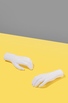 Minimalistic composition in yellow and grey colors with white plastic hands. Creative concept.