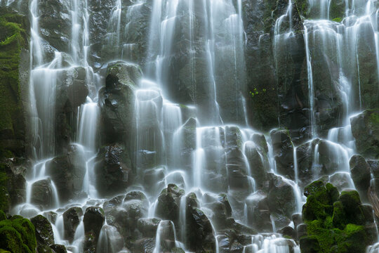 Waterfall cascading down  mossy rocky cliff in forest of Oregon USA