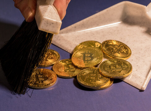 Brushing bitcoins into a dustpan as concept for the collapse in value of cyber coins and digital currency