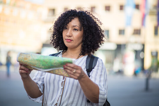 Woman standing on street with map in hands.