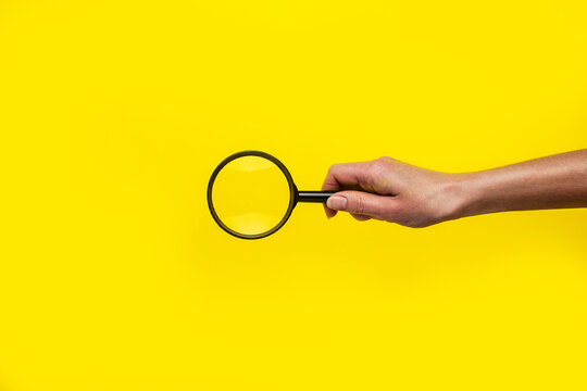 female hand holds a magnifying glass loupe on a yellow background