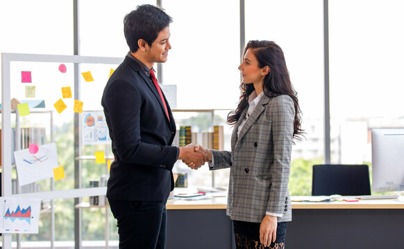 Young long black hair happy confident caucasian female businesswoman in gray stripe formal suit stand smiling handshaking with asian male businessman in black suit with red necktie in company office