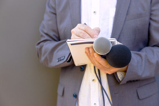 Journalist at media event or news conference, holding microphone, writing notes. Broadcast journalism concept.