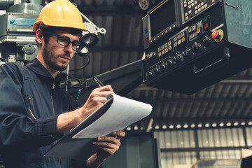 Skillful factory worker working with clipboard to do job procedure checklist . Factory production...