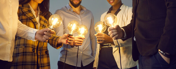 Background with young multiethnic business team holding glowing vintage Edison lightbulbs. Multiracial men and women join shining electric light bulbs for teamwork and sharing creative ideas - fototapety na wymiar