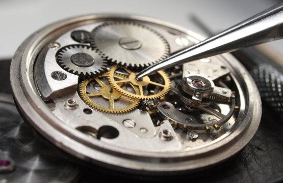vintage watch under repair, display of parts of vintage watch mechanism: dial, gears, screws, balance wheel and springs